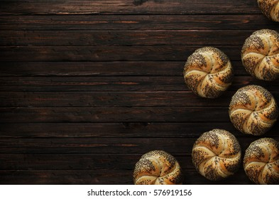 Crusty fresh kaiser rolls on wooden table.