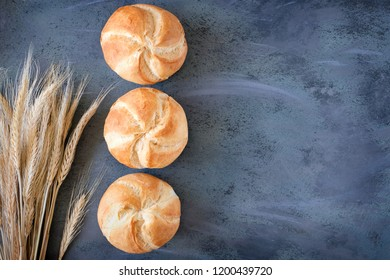 Crusty round bread rolls, known as Kaiser or Vienna rolls with a bunch of wheat ears on dark grey background, flat lay with copy-space