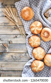 Crusty round bread rolls, known as Kaiser or Vienna rolls scattered on linen towel on rustic wood, flat lay with copy-space