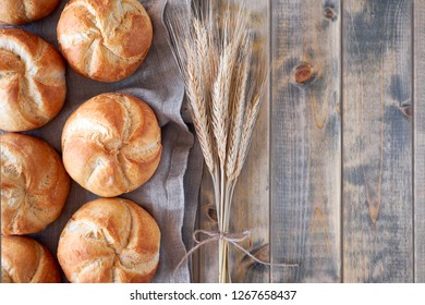 Crusty round bread rolls, known as Kaiser or Vienna rolls scattered on linen towel on rustic wood, flat lay