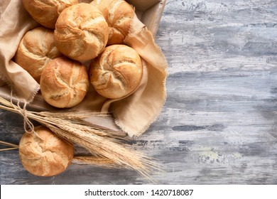 Crusty round bread rolls, known as Kaiser or Vienna rolls on linen towel, flat lay on rustic background with text space