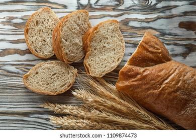 Crusty sliced bread wheat ears on wooden surface.