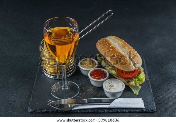 crusty white bread with sesame seeds, flavored with smoky ribsteak bbq, barbeque sauce, lettuce, tomato, three sauces, chips in a metal basket, white wine, tasty set