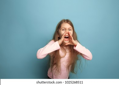 The cry. The angry screaming teen girl on a blue studio background. Facial expressions and people emotions concept. Trendy colors. Front view. Half-length portrait