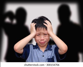 Crying asian boy with his fighting parents in the background
