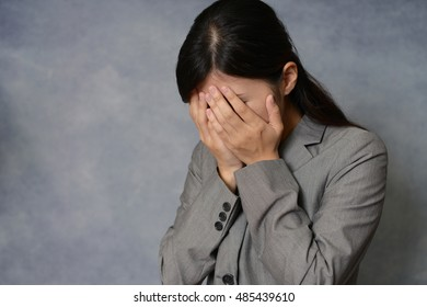 Crying Asian business woman