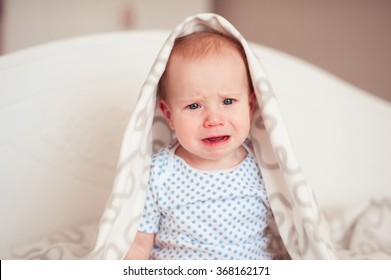Crying baby boy 8-9 months sitting in bed looking at camera. Sadness. Childhood.
