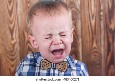 Crying baby boy in a plaid shirt with a bow tie.