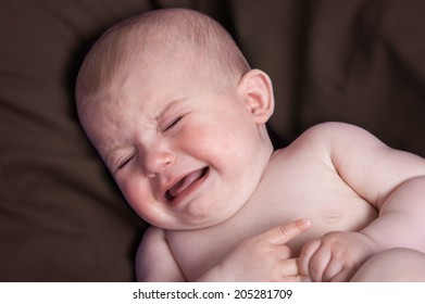 Crying baby distressed on brown pillow.