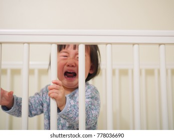 Crying Baby girl in cot bed