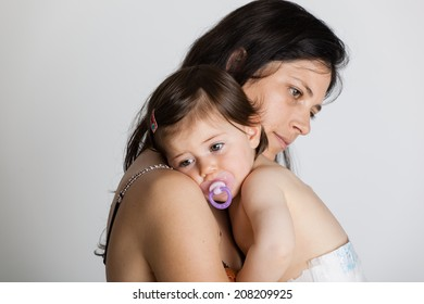 Crying baby girl with her mother isolated on white