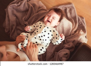 Crying baby on mother hands in room. Motherhood. Stomach ache.