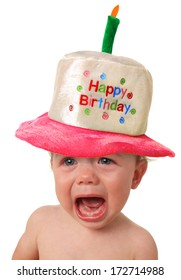 Crying baby wearing a Happy Birthday hat.