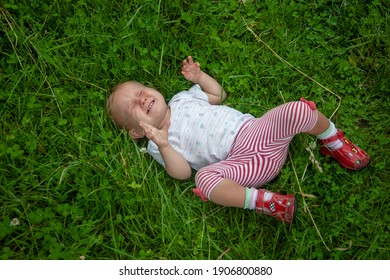 Crying baby (whims baby) on the green grass.
