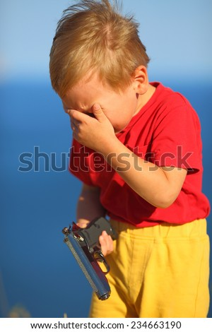 crying  boy with a gun on the coast