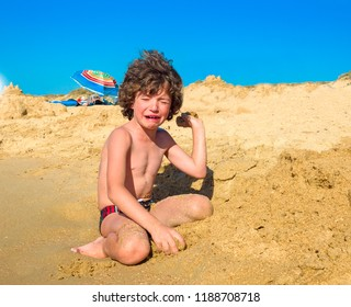 Crying boy on the beach. A small child sitting by the sea and hysterically crying