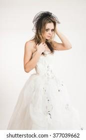 Crying bride, wearing ragged wedding dress