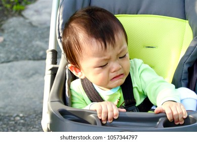The crying child is sitting on his roller baby carriage
