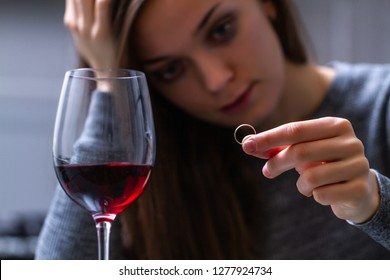 Crying, divorced woman holding a wedding ring and drinking alone a red wine because of adultery, betrayal and failed marriage. Divorce concept. Relationship and love end.