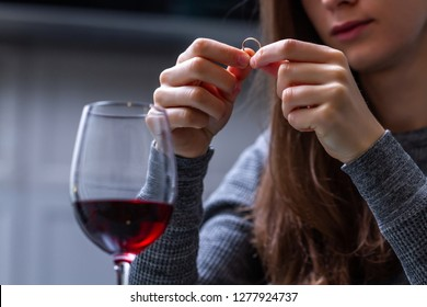 Crying, divorced woman holding a wedding ring and drinking alone red wine because of adultery, betrayal and failed marriage. Divorce concept.