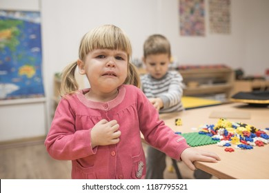 Crying girl and boy playing in kindergarten