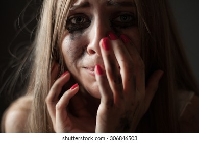 Crying girl on a black background. Closeup. Shallow depth of field