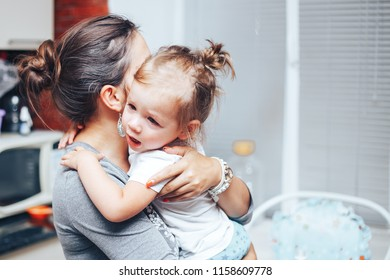 crying girl on mother hands at home