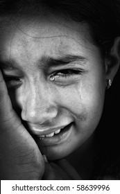 Crying girl, tears on cheeks, low light key, added grain, black and white