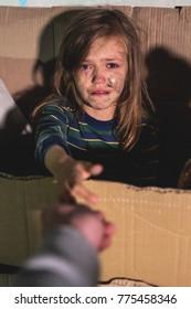 Weine obdachlose Junge Mädchen, die in der Karton sitzen und den Arm verbreiten.