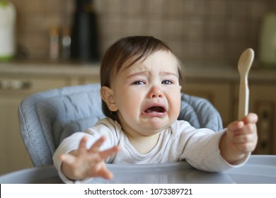 Crying hungry little baby with tears in eyes sitting in the high feeding chair at kitchen holding spoon in his hand, gesture