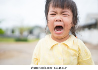 Crying little asian girl on the park.sad and depressed little girl in the park.