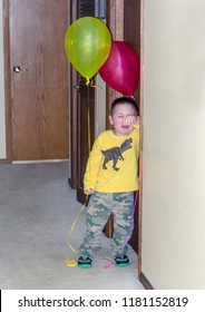 crying little boy with balloons stands outside a door