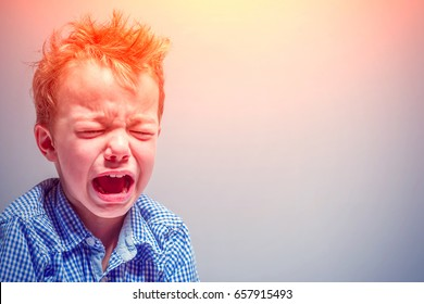 Crying little boy on a gray background in the sunlight