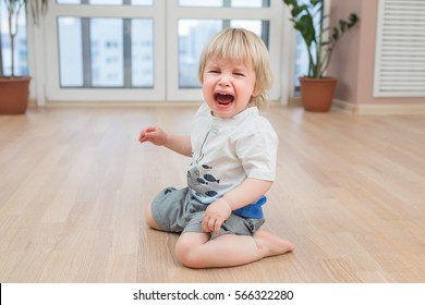 Crying little cute child on the floor at home. 2 years old Toddler or baby sadness.