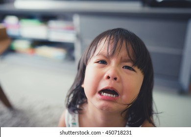 Crying little girl at home.