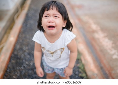 crying little girl on street.Little asian girl fall on street and crying.