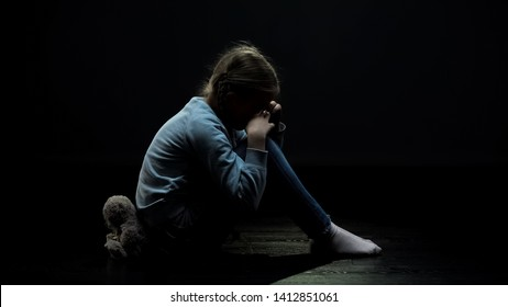 Crying little girl sitting back to teddy bear in dark abandoned room, loneliness