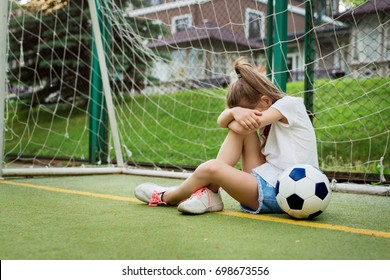 Crying ltittle girl who is playing football, hiding her face while being upset to miss goal in gates. Pretty kid wearing white t-shirt, jean shorts and sport shoes, playing football. Children, sport