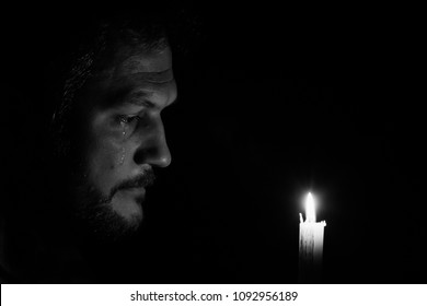 Crying male looking at candle