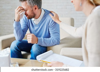 Crying man with handkerchief sitting by his psychologist