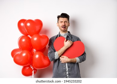 Crying man standing single and lonely on Valentines day, hugging heart cutout and sobbing miserable, being heartbroken and rejected by lover, white background