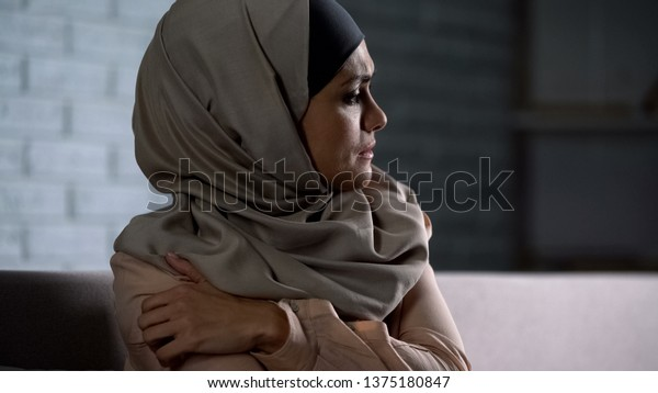 Crying muslim female holding painful hand, suffering from husband violence