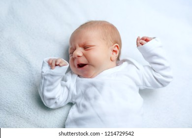 Crying newborn baby boy or girl on changing table