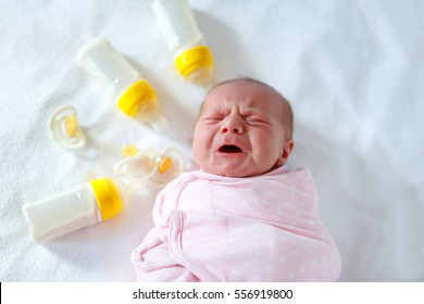 Crying newborn baby girl with nursing bottles. Formula drink for babies. New born child, little girl laying in bed. Family, new life, childhood, beginning, bottle-feeding concept.