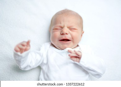 Crying newborn baby on changing table. Cute little girl or boy two weeks old. Dry and healthy body and skin concept. Baby nursery.
