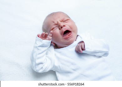 Crying newborn baby on changing table. Cute little girl or boy two weeks old. Dry and healthy body and skin concept. Baby nursery