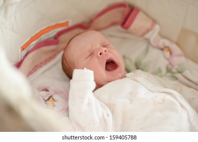 crying newborn is laying in crib