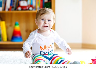 Crying sad baby girl playing with educational toys in nursery. hysteric healthy child having fun with colorful different toys at home. Baby development and first steps, learning to play and to grab.
