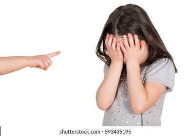 Crying school girl covering hear eyes being bullied. Finger pointing someone. Isolated on a white background.