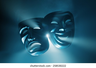Crying and smiling masks in hazy light.